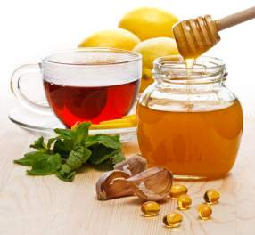 Tea with lemon, garlic, capsules and honey on white background